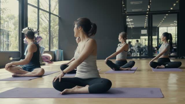 stockvideo's en b-roll-footage met groep jonge sportieve mensen die van yogales oefenen - yogastudio