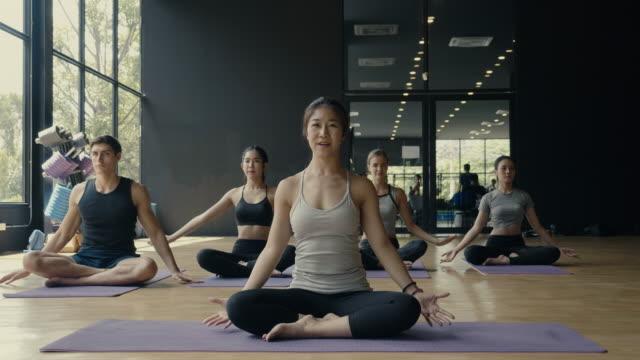 gruppe junger sportler, die yoga-unterricht praktizieren - yogastudio stock-videos und b-roll-filmmaterial