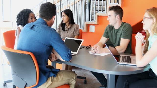 vidéos et rushes de groupe de démarrage de jeunes entrepreneurs d'affaires lors d'une réunion - hot desking