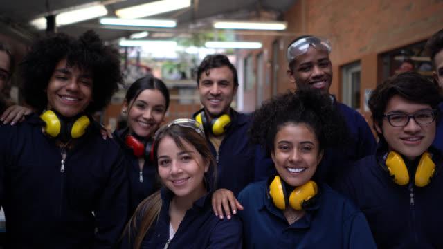 vídeos de stock, filmes e b-roll de grupo de jovens estudantes em uma aula de oficina usando roupas de trabalho protetores sorrindo para a câmera - protetor de ouvido