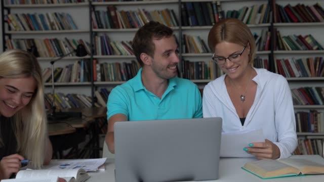 Gruppe junger Studenten in der Bibliothek, die mit Texten Bücher und Laptop lachen und lächeln