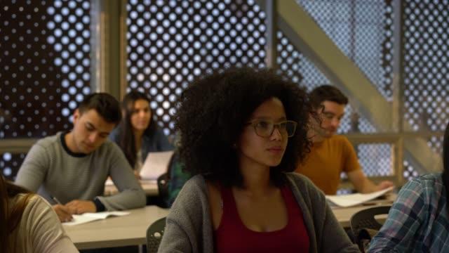 vidéos et rushes de groupe de jeunes étudiants au cours de la classe au collège payant attention et prendre des notes - jeunes hommes