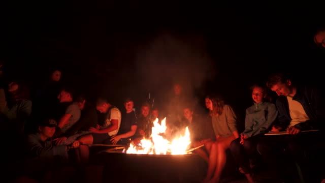group of young teens around a bonfire at night - 16 17 år bildbanksvideor och videomaterial från bakom kulisserna