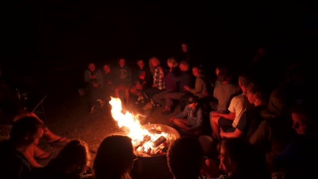 stockvideo's en b-roll-footage met group of young teens around a bonfire at night - 16 17 jaar