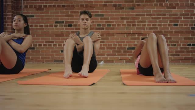 stockvideo's en b-roll-footage met een groep van jonge tieners doen van sit ups in een studio-sportschool - oefeningen met lichaamsgewicht
