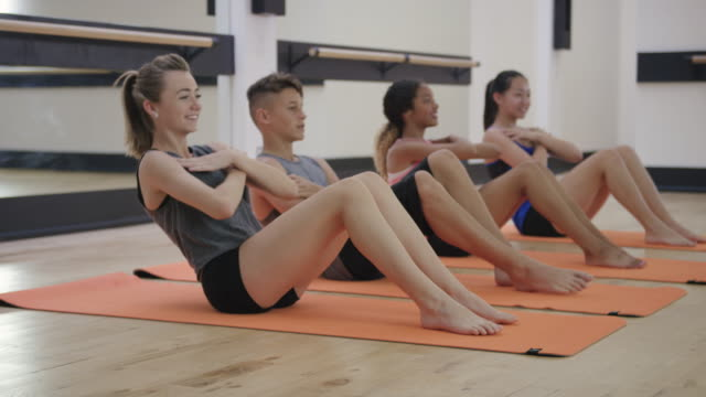 a group of young teens doing sit ups in a studio gym - relaxation exercise stock videos and b-roll footage