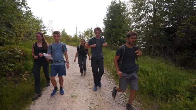 group of young teens hiking in the woods - 16 17 år bildbanksvideor och videomaterial från bakom kulisserna
