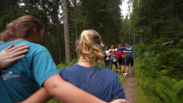 group of young teens walk along path while teambuilding - hobby stock-videos und b-roll-filmmaterial