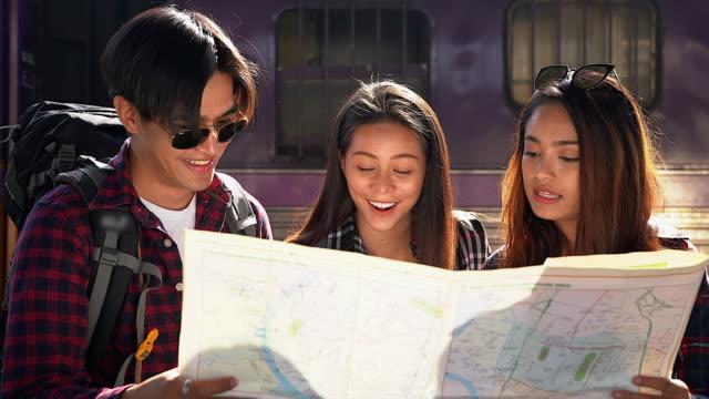vídeos y material grabado en eventos de stock de grupo de jóvenes viajeros que buscan mapa y discutir su viaje en la estación de tren. - tourism