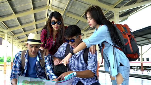 Group of young traveller looking map and discuss their trip at the train station.