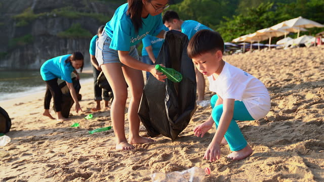group of young volunteers helping to keep nature clean and picking up the garbage from a sandy shore. - picking stock videos & royalty-free footage