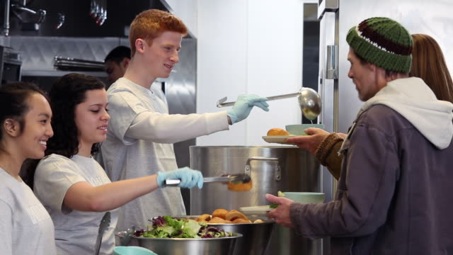 ms ds group of young volunteers serving food at soup kitchen in homeless shelter / richmond, virginia, united states - volontär bildbanksvideor och videomaterial från bakom kulisserna