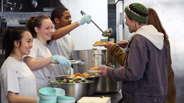 stockvideo's en b-roll-footage met ms ds group of young volunteers serving food at soup kitchen in homeless shelter / richmond, virginia, united states - schenking