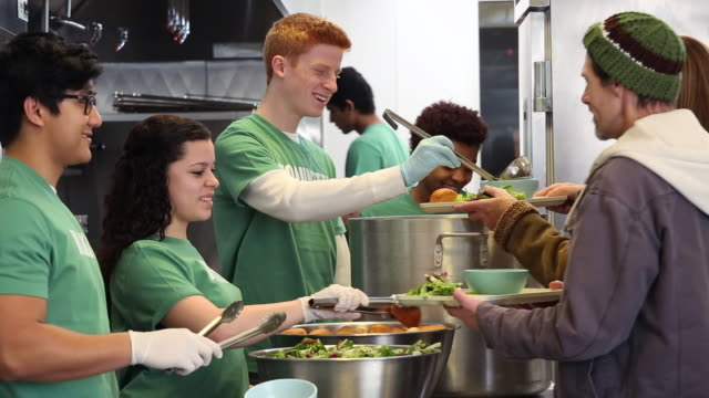 ms ds group of young volunteers serving food at soup kitchen in homeless shelter / richmond, virginia, united states - soup kitchen stock videos & royalty-free footage