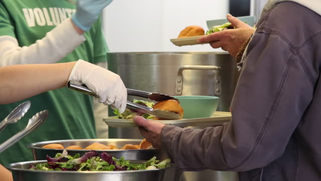 stockvideo's en b-roll-footage met cu ds group of young volunteers serving food at soup kitchen in homeless shelter / richmond, virginia, united states - schenking