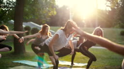 Group of young woman in sportswear are standing in yoga position on one leg