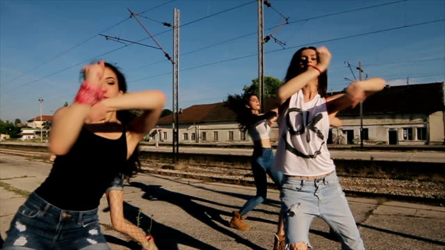 Group of young women dancing hip hop on railway station