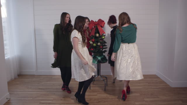 Group of young women in dresses dancing around christmas tree