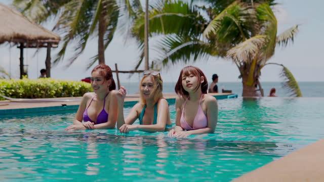 gruppe junger frauen in kleinen sexy bikinis, die spaß am pool im wasser haben - three people stock-videos und b-roll-filmmaterial