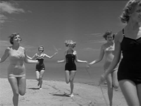 B/W 1951 group of young women in swim suits jumping rope on beach / St. Petersburg, FL / doc.