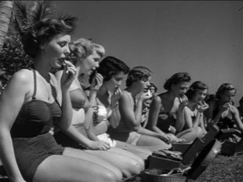 vidéos et rushes de b/w 1951 group of young women in swimsuits sitting on grass applying lipstick / st. petersburg, fl - seulement des femmes