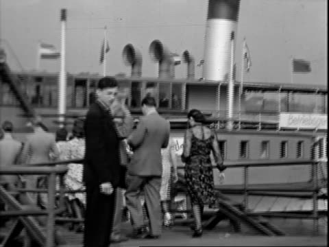 group of young women standing on street, street car stopping beside them / well-dressed white people standing on pier by river, waiting for boat,... - 1942年点の映像素材/bロール