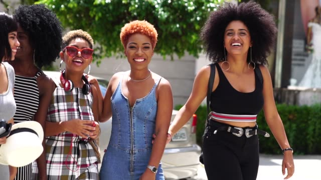 vídeos de stock e filmes b-roll de group of young women walking in the street - afro americano