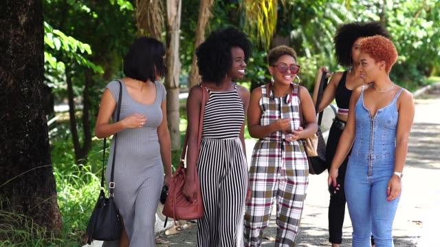gruppo di giovani donne che camminano per strada - afro video stock e b–roll