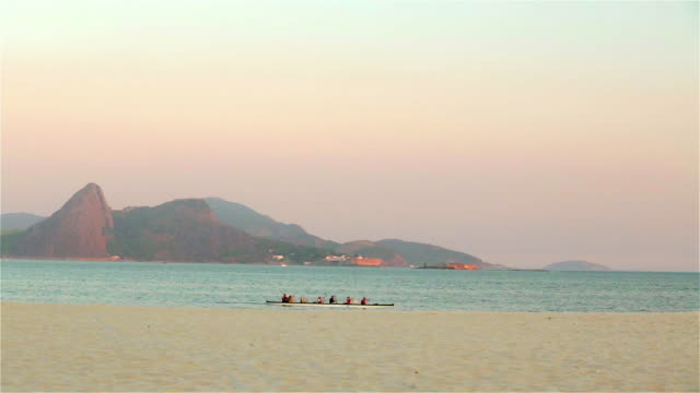 Group on scenic canoeing trip row past Sugarloaf Mountain off Rio coast
