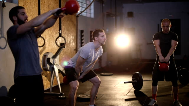 group pf people doing a kettlebell workout together - attrezzatura per esercizio fisico video stock e b–roll