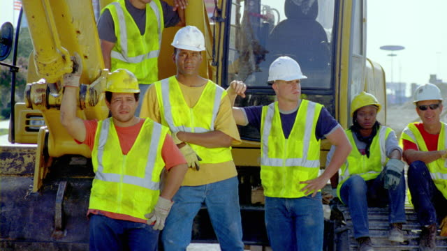 ms, pan, group portrait of construction workers standing and sitting by earth mover, san antonio, texas, usa - bauarbeiter stock-videos und b-roll-filmmaterial