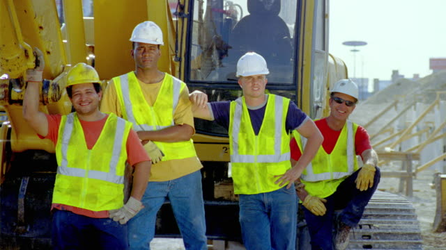 MS, group portrait of construction workers standing by heavy equipment, San Antonio, Texas, USA