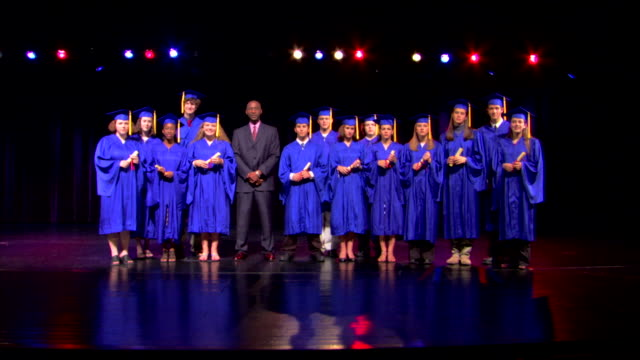 stockvideo's en b-roll-footage met group portrait of graduates standing on stage with their diplomas. - afstudeer toga