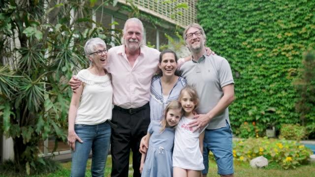 vidéos et rushes de portrait de groupe des grands-parents, des parents et des petites-filles - cadrage en pied