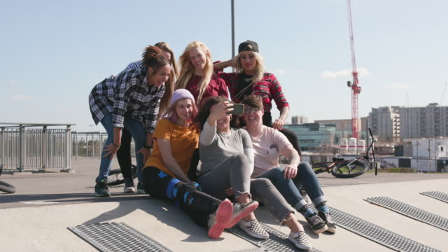 group portrait of young female bmx riders hanging out together taking a selfie - youth culture stock videos & royalty-free footage