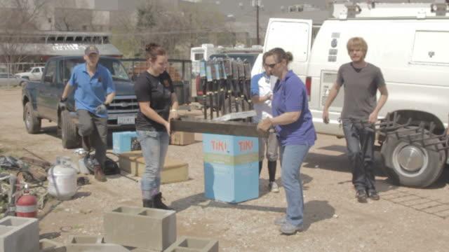 vidéos et rushes de group puts grill on top of cinder blocks - parpaing
