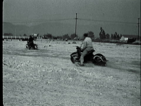 montage group riding their motorcycles through rough terrain and then inspecting a bike and line of motorcycles ready to ride / california, united states - 1940 1949 video stock e b–roll