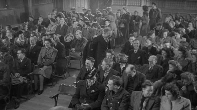 pan group seating themselves in a packed town hall before a speaker on stage begins to address the audience / united kingdom - public speaker stock videos and b-roll footage