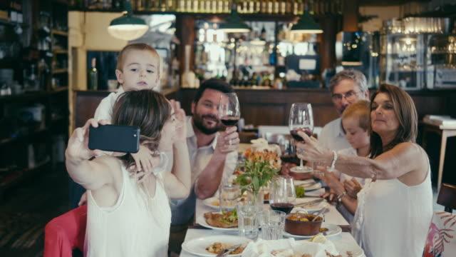 レストランでディナーパーティーを開く多世代のラテンアメリカの家族のグループ自分撮り - 自分撮り点の映像素材/bロール