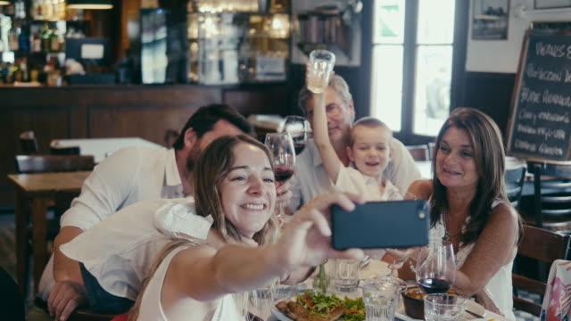 vídeos y material grabado en eventos de stock de selfie en grupo de una familia latinoamericana de varias generaciones que tiene una cena en el restaurante - sentado