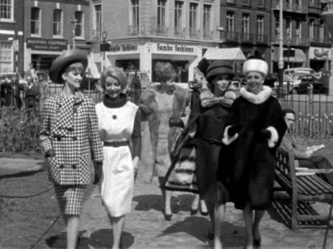 vídeos de stock e filmes b-roll de group shot of models wearing the latest fashions walking along a path in a small london park 1963 - saia
