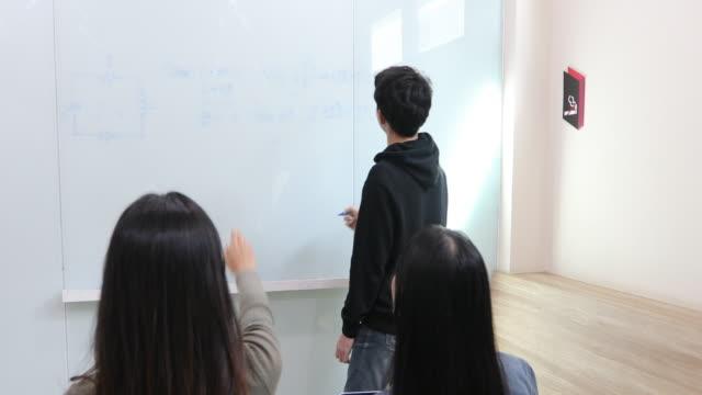 gruppe schüler erheben ihre hände zu einem freund fragen für den unterricht am whiteboard im klassenzimmer - trigonometrie stock-videos und b-roll-filmmaterial