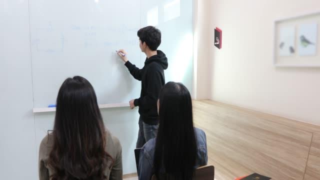 gruppenschüler heben ihre hände, um einem freund fragen für den unterricht am whiteboard im unterricht zu stellen - trigonometrie stock-videos und b-roll-filmmaterial