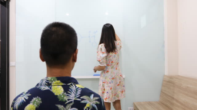 Group Students raise their hands to ask a friend questions for teaching at whiteboard in classroom