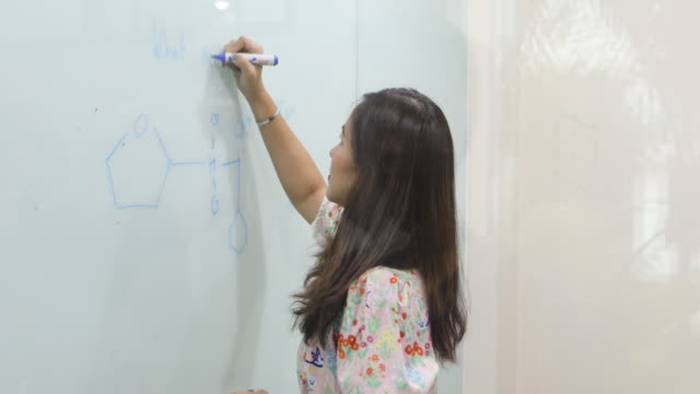 group students raise their hands to ask a friend questions for teaching at whiteboard in classroom - corso di matematica video stock e b–roll