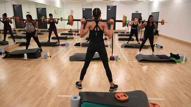 group takes part in a high energy barbell class just after midnight at an indoor group exercise studio at park road pools & fitness on may 17, 2021... - healthy lifestyle stock videos & royalty-free footage