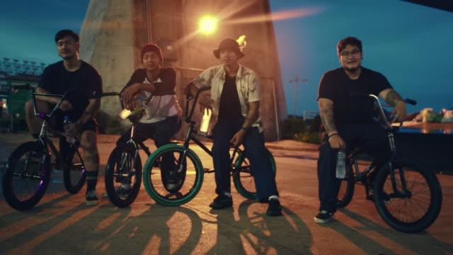 公園で自転車に乗っている友人の観光客のグループ10代。 - スタントバイク点の映像素材/bロール