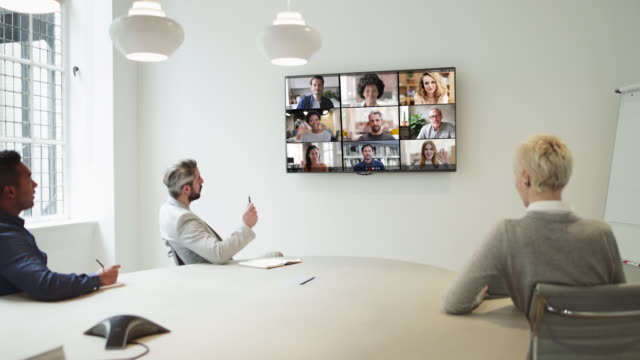 group using video conferencing technology in office for video call with colleagues abroad - employee engagement stock videos & royalty-free footage