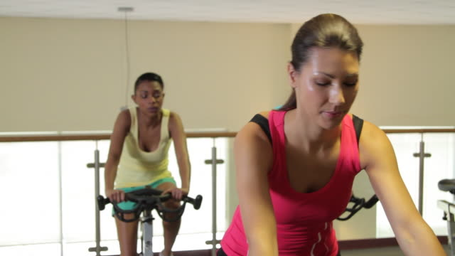 group working out on bicycles in a gym - インドアサイクリング点の映像素材/bロール