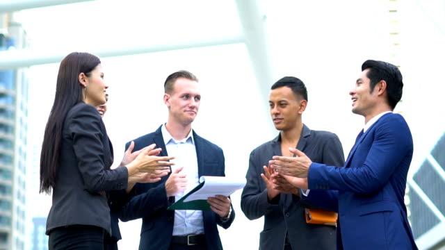 vídeos y material grabado en eventos de stock de grupo empresarial jóvenes trabajadores comunican y cepillado de inicio nuevo proyecto empresarial en el exterior - compromiso de los empleados